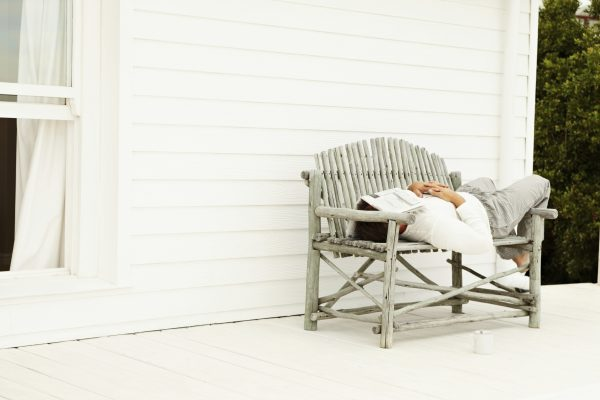 Man sleeping on a bench on the porch outside his home , newspaper on face
